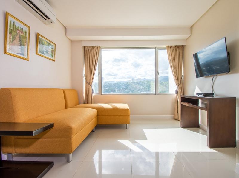 セブ島のアリシアアパーテルの客室 ワンベッドルームデラックスのソファとテレビ