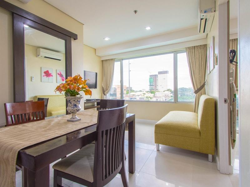 セブ島のアリシアアパーテルの客室 ワンベッドルームデラックスプレミアムのソファとテーブル