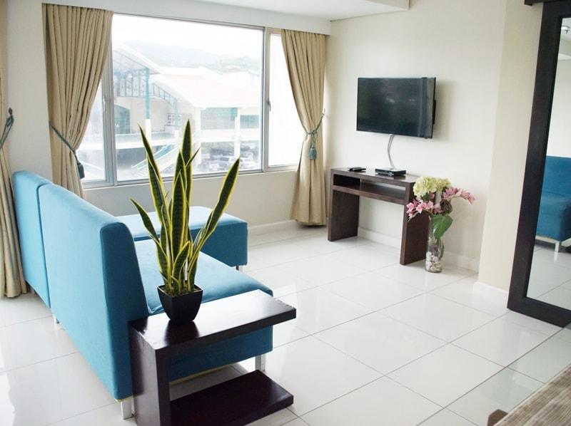 セブ島のアリシアアパーテルの客室 ワンベッドルームスーペリアのソファとテレビ