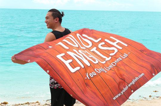 YOLOL ENGLISHのフラッグを持つフィリピンの男性